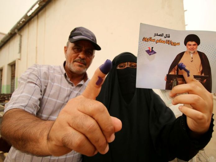 People show their ink-stained fingers after voting in Basra Controversial cleric emerges as likely winner in Iraq's national election Controversial cleric emerges as likely winner in Iraq's national election skynews iraq election 4307422
