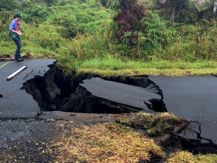 A geologist inspects cracks on a road following the eruption of Kilauea volcano Hawaiians warned of 'powerful' eruptions within hours Hawaiians warned of 'powerful' eruptions within hours skynews kilauea volcano hawaii 4313547