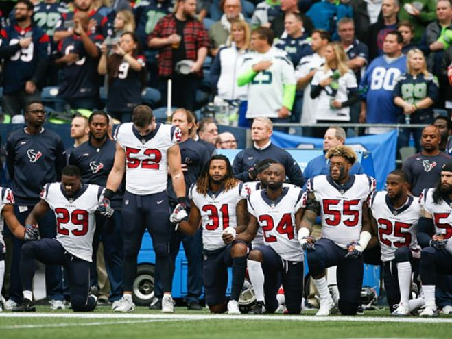 Members of the Houston Texas kneel before their games at the Seattle Seahawks