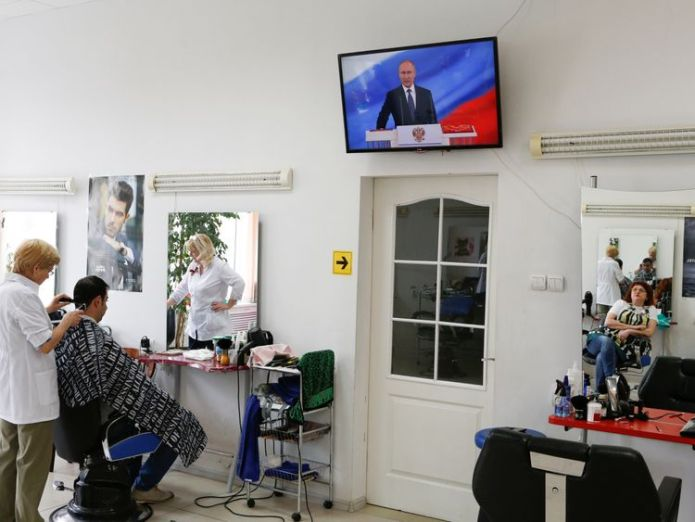 A hairdresser, who watches a ceremony to inaugurate Vladimir Putin as President of Russia, is reflected in a mirror at a hair design salon in Stavropol, Russia May 7, 2018. REUTERS/Eduard Korniyenko vladimir putin has been sworn in as russian president Vladimir Putin has been sworn in as Russian president skynews russia putin inauguration 4303226
