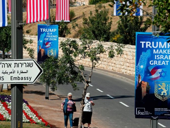 People walk on May 11, 2018 near the compound of the US consulate in Jerusalem, which will host the new US embassy, as posters praising the US president hang in the street Middle East peace unlikely if Donald Trump takes sides Middle East peace unlikely if Donald Trump takes sides skynews trump israel embassy 4306975