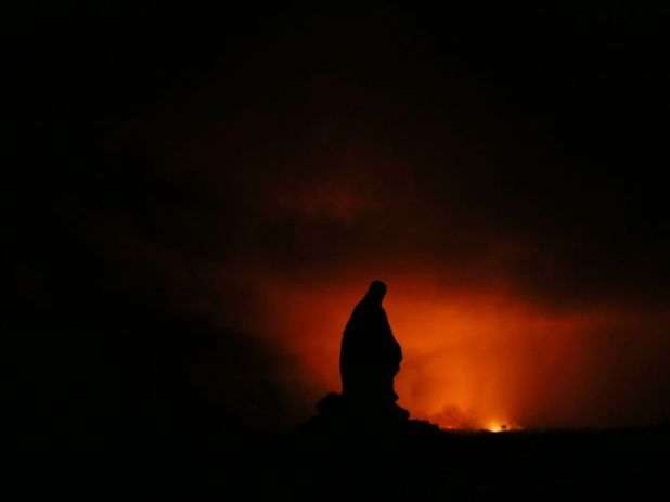 A Virgin Mary statue is silhouetted by the glow of a lava eruption