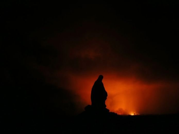 A Virgin Mary statue is silhouetted by the glow of a lava eruption Roads ripped up by rumbling Big Island Hawaii volcano Roads ripped up by rumbling Big Island Hawaii volcano skynews virgin mary statue 4312274