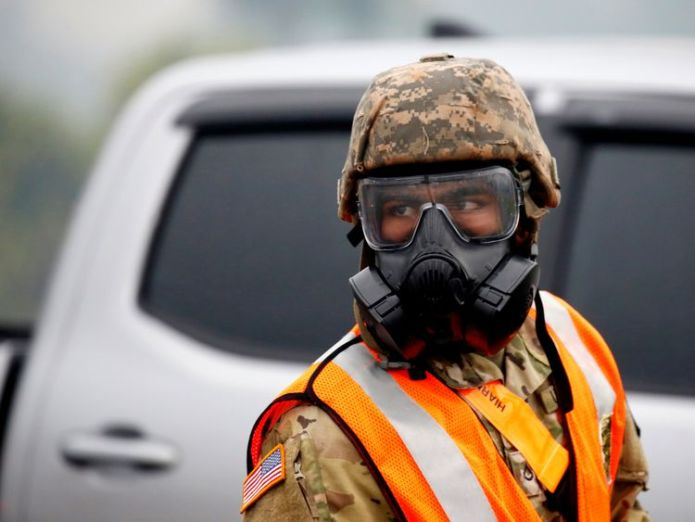 A soldier of the Hawaii Army National Guard wears a mask to protect himself from volcanic gases Hawaiians warned of 'powerful' eruptions within hours Hawaiians warned of 'powerful' eruptions within hours skynews volcano kilauea hawaii 4313548