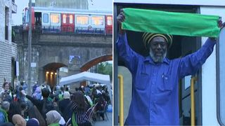 The train driver held up a green scarf in tribute to the Grenfell anniversary gathering