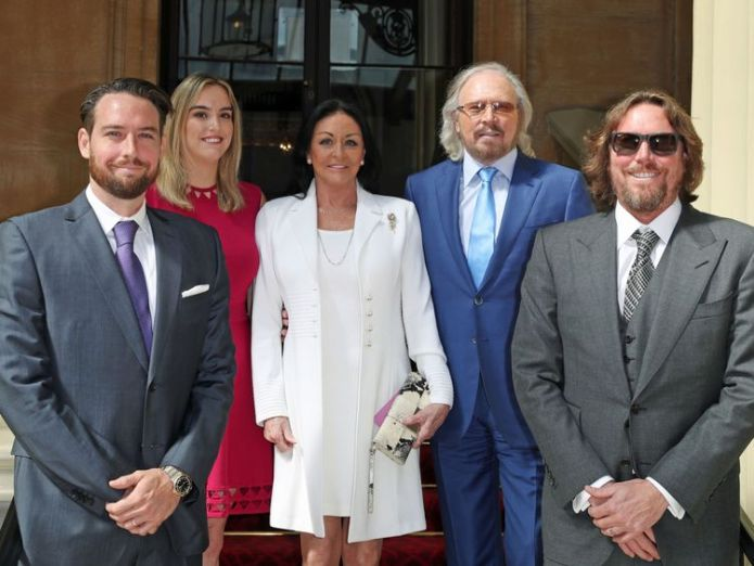 Singer and songwriter Barry Gibb, with his wife, Linda, and children, Michael (left), Alexandra and Ashley (right) at Buckingham Palace Bee Gee Barry Gibb 'thought knighthood was a wind-up' Bee Gee Barry Gibb 'thought knighthood was a wind-up' skynews barry gibb investiture ceremony 4345989