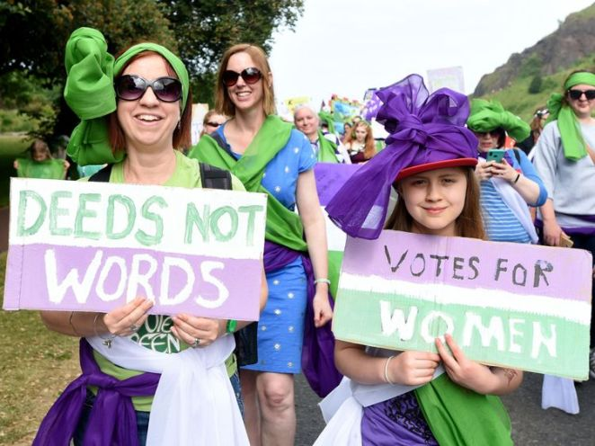 Marchers in Edinburgh carry Deeds Not Words signs