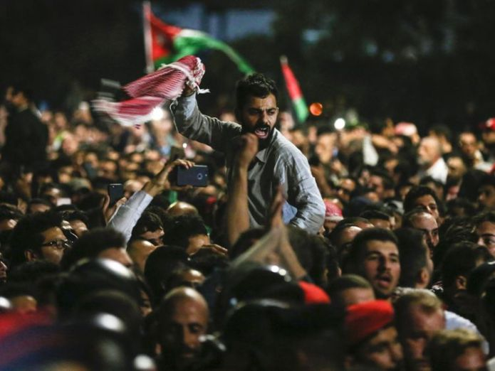 Jordanian protesters shout slogans and raise a national flag during a demonstration jordan's king appoints new prime minister as protests rage Jordan's king appoints new prime minister as protests rage skynews jordan protests 4327028