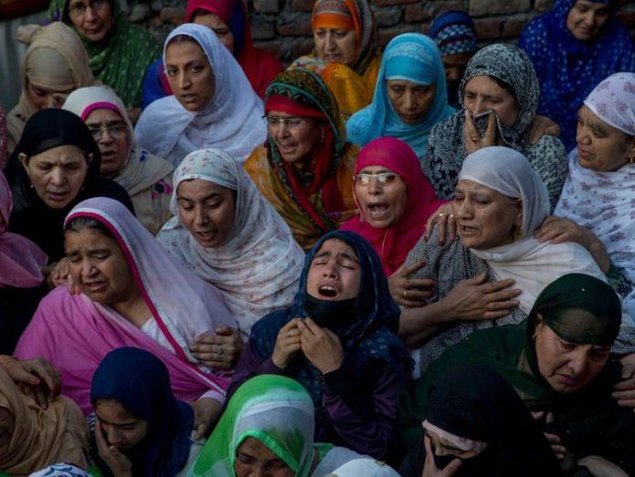 Kashmiri women grieve near the body of Qaiser Amin Bhat, during his funeral  Shotguns fired by police at funeral of Kashmir protester Shotguns fired by police at funeral of Kashmir protester skynews kashmir funeral 4326430