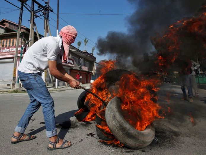 A masked protester burns tires during the funeral of Kaisar Ahmad Bhat in Srinagar Shotguns fired by police at funeral of Kashmir protester Shotguns fired by police at funeral of Kashmir protester skynews kashmir protests 4326422