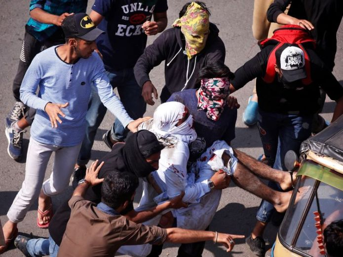 Protesters carry an injured man who was hit by a Central Reserve Police Force (CRPF) vehicle Shotguns fired by police at funeral of Kashmir protester Shotguns fired by police at funeral of Kashmir protester skynews kashmir protests 4326425