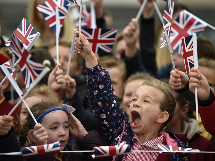 Schoolchildren wave flags as they greet the Queen and Meghan
