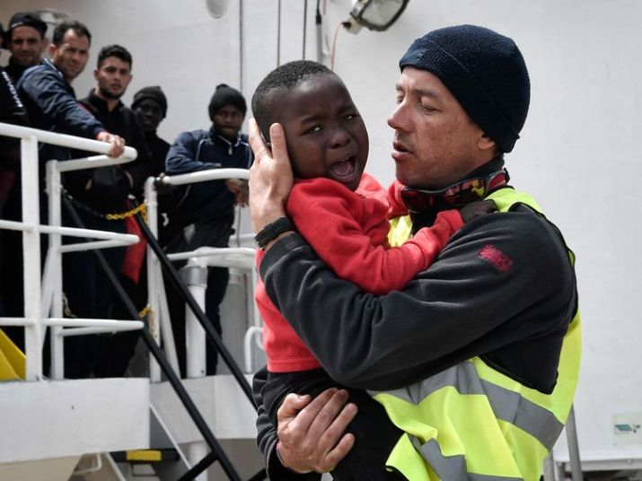 A helper from Doctors Without Borders (MSF) holds a Nigerian child as he and his mother (unseen) disembark from the MV Aquarius upon its arrival at the Sicilian port of Messina last month