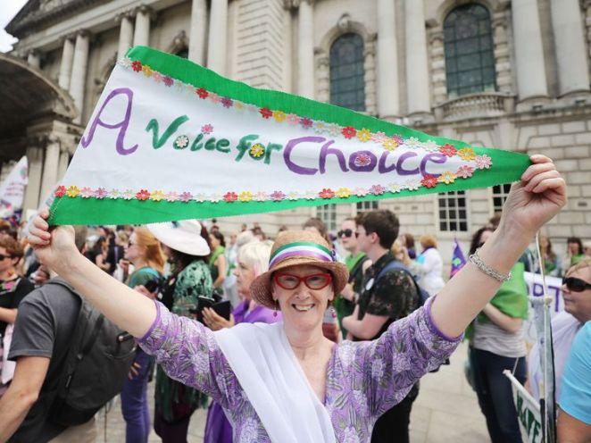 A woman marches in Northern Ireland, with an abortion campaign banner