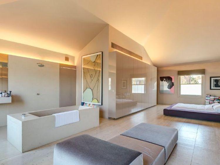The open-plan bathroom boasts a cast stone bath
