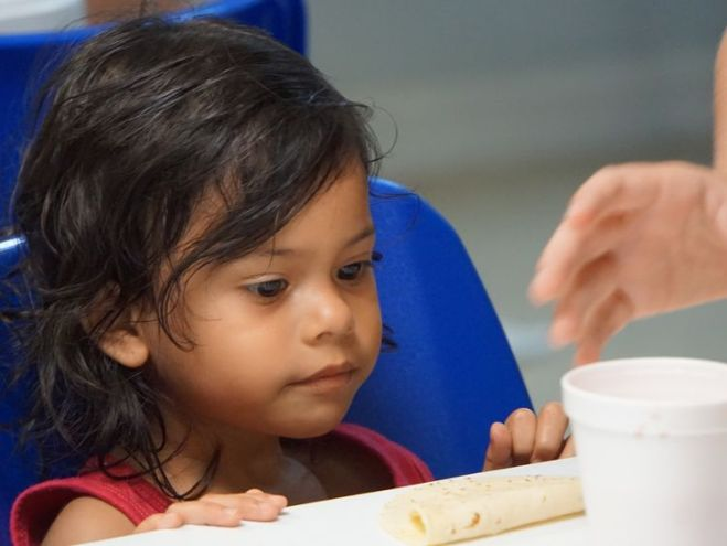 A young girl is given some soup at a migration centre in Texas