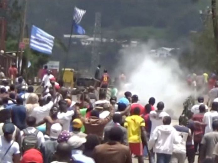 Protesters waving Ambazonian flags as they move forward towards barricades and police amid tear gas in the English-speaking city of Bamenda  'Grave abuses' as 180,000 people displaced in Cameroon skynews cameroon protests francophone 4366367