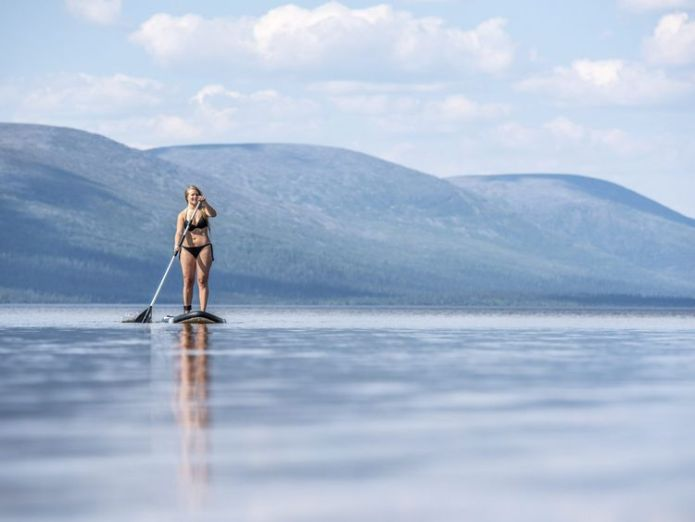 A bikini-clad woman on a surfboard in Finnish Lapland  Arctic Circle wildfires rage on as blistering heat takes hold of northern Europe skynews finland weather 4367373