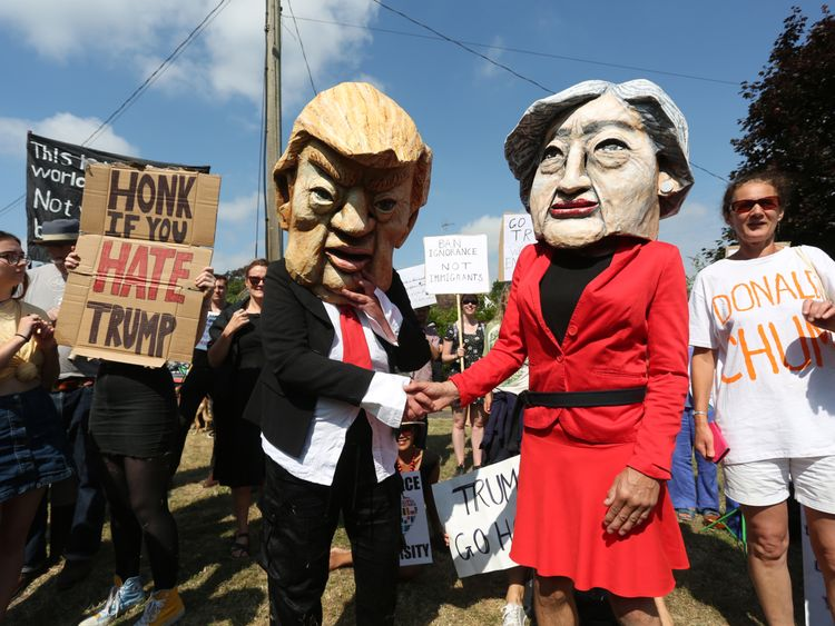Protesters wearing masks depicting US President Donald Trump and Britain's Prime Minister Theresa May join other protesters against the UK visit of US President Donald Trump demonstrate outside Chequers