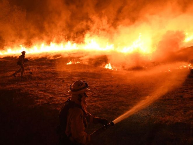 Firefighters conduct a controlled burn to defend houses against flames from the Ranch fire, as it continues to spreads towards the town of Upper Lake, California on August 2, 2018. - Thousands of firefighters in California made some progress against several large-scale blazes that have turned around 200,000 acres (80,940 hectares) into an ashen wasteland, destroyed expensive homes, and killed eight fire personnel and civilians in the most populous US state. (Photo by Mark RALSTON / AFP) (Photo c