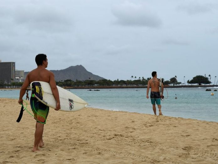 Surfers walk to the water to paddle out as Hurricane Lane approaches Honolulu, Hawaii, U.S. August 23, 2018. REUTERS/Hugh Gentry  Hawaii in lockdown as centre of storm nears skynews hawaii hurricane lane 4399327