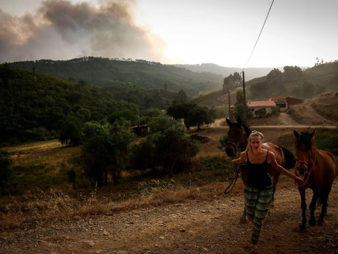 A woman pulls two horses as smoke columns rise due to a wildfire close to Monchique in the Portuguese Algarve, on August 4, 2018. - A village in a tourist area in southern Portugal was evacuated as more than 400 firefighters tackled a forest fire, emergency services said. With Europe still on high alert during a record-breaking and deadly heatwave, Portugal has seen the mercury reach almost 46 degrees Celcius -- with more hot days to come. (Photo by CARLOS COSTA / AFP) (Photo credit should read   Portugal roasts on country's hottest day in 18 years skynews portugal weather 4381426