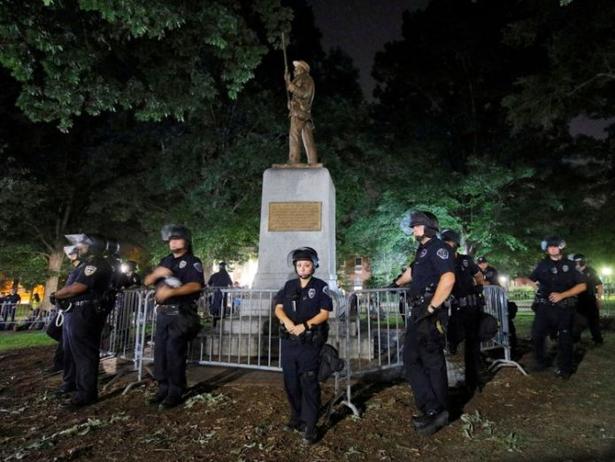 Police wearing riot gear guard a statue of a Confederate soldier nicknamed Silent Sam on the campus of the University of North Carolina during a demonstration for its removal in Chapel Hill, North Carolina, U.S. August 22, 2017. REUTERS/Jonathan Drake TPX IMAGES OF THE DAY  Students tear down 'Silent Sam' Confederate statue in North Carolina skynews silent sam statue 4396752
