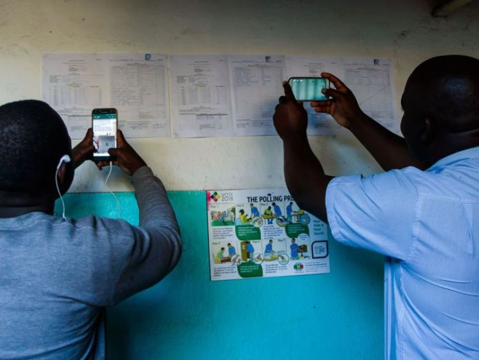 People take pictures of the results at a polling station in Kambuzuma Township, Harare