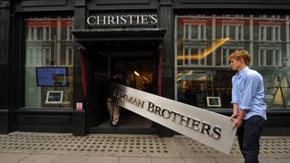 Employees pose for photographers with a Lehman Brothers company sign at Christie's auction house in London on September 24, 2010. The sign will be sold as part of the 'Lehman Brothers: Artwork and Ephemera' sale in London on September 29. AFP PHOTO / BEN STANSALL (Photo credit should read BEN STANSALL/AFP/Getty Images)   Next financial crisis 'has begun and will be worse than 2008 crash,' economists warn skynews lehman lehman brothers 4420667