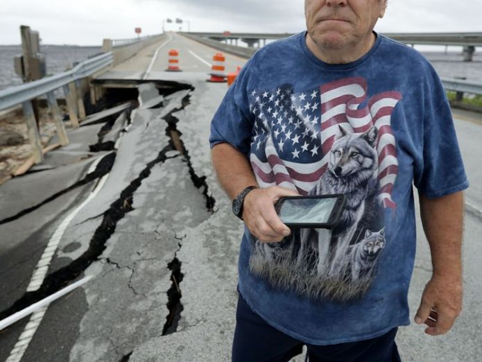Residents stop to photograph a section of the Highway 17 exit ramp that remains closed a day after Hurricane Florence's storm surge washed it out September 15, 2018 in New Bern, North Carolina  Disaster declared in North Carolina as Tropical Storm Florence dumps 'epic' amount of rainfall skynews florence storm hurricane 4422012