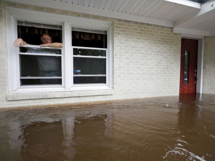 Obrad Gavrilovic peers out the window of his flooded home while considering whether to leave with his wife and pets, as waters rise in Bolivia, North Carolina, U.S  Five arrested for looting as Florence kills 13 in North and South Carolina skynews north carolina florence 4422866