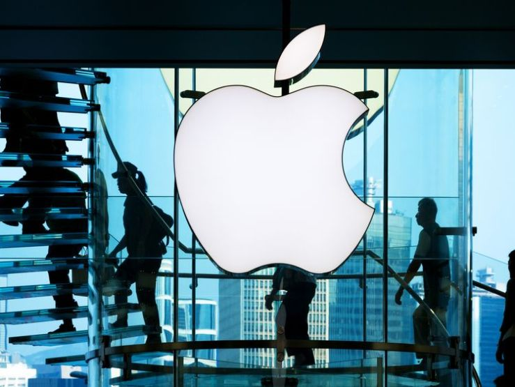 Employees walk past the big Apple sign in front of a shop