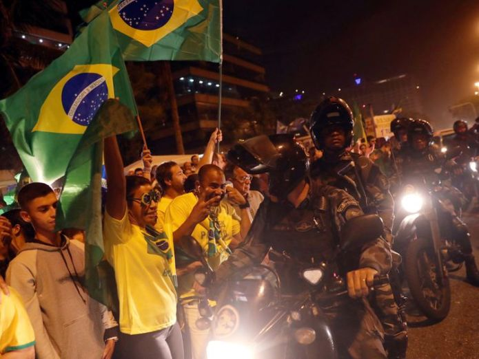 Police ride past supporters of Mr Bolsonaro in Rio de Janeiro hours before his success was revealed  Brazil's far-right candidate Jair Bolsonaro storms presidential election round skynews bolsonaro brazil election 4447056