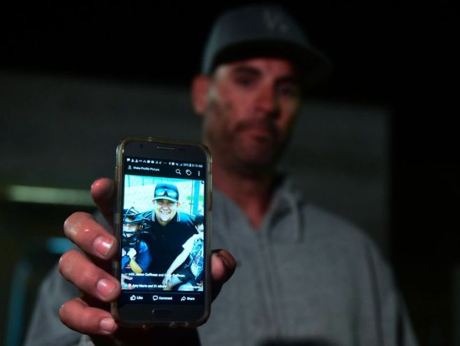 Jason Coffman shows a photo of his son Cody who was at the bar but has not been seen.