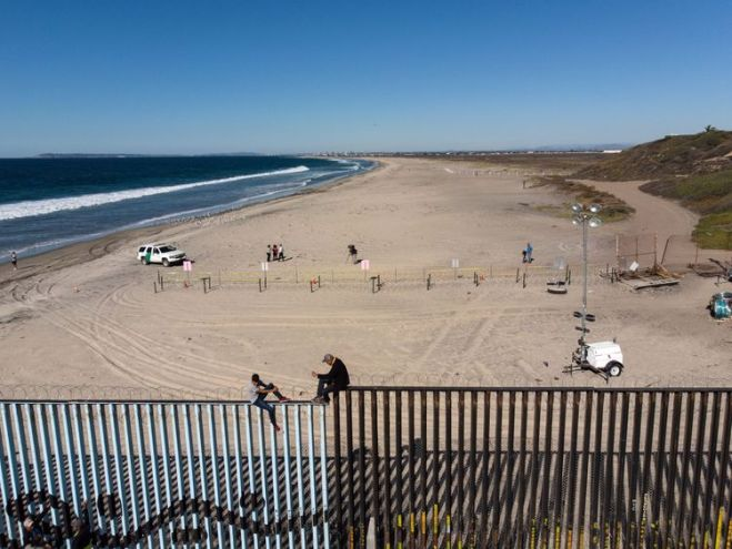 Two members of the migrant caravan sit on the US border fence before it is sealed