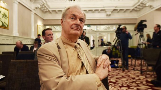 US born broadcaster Paul Gambaccini listens as former British Conservative MP Harvey Proctor addresses a press conference in central London