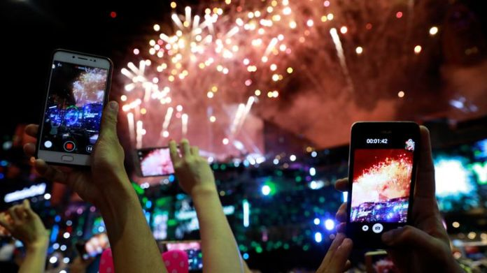 Tourists and locals watch fireworks as they attend the New Year's countdown party in Bangkok, Thailand, December 31, 2018. REUTERS/Soe Zeya Tun