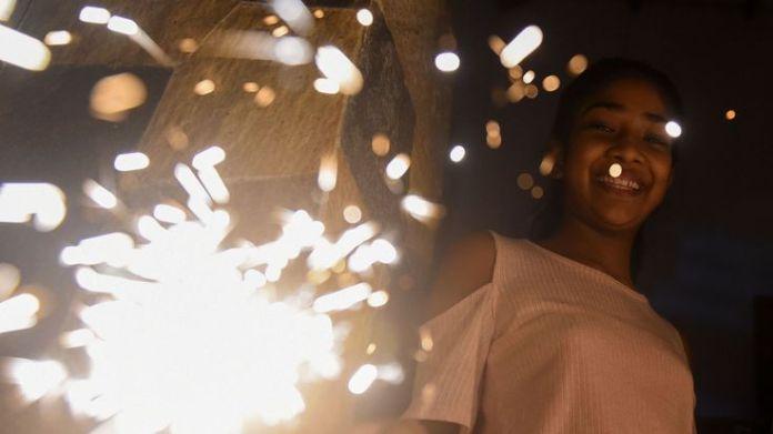A young woman holds a sparkler during New Year's celebrations in Colombo, Sri Lanka, on January 1, 2019. (Photo by ISHARA S. KODIKARA / AFP) (Photo credit should read ISHARA S. KODIKARA/AFP/Getty Images)