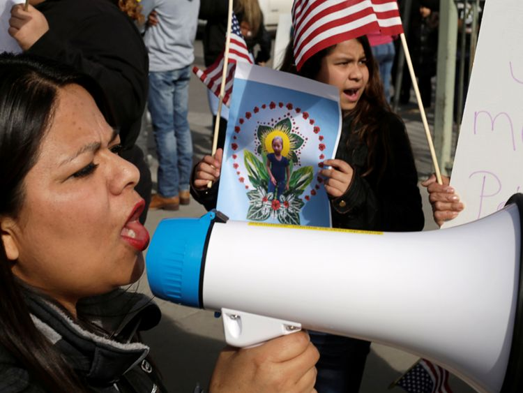 A woman holds a picture of Jakelin Caal, who died in US custody after crossing illegally from Mexico to the US