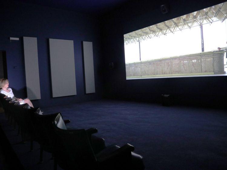 A woman views a video piece by artist Naeem Mohaiemen at Tate Britain