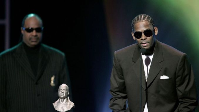 Singer R. Kelly accepts the Stevie Wonder Award with Stevie Wonder (L) presenting onstage at the 20th Annual Soul Train Music Awards at the Pasadena Civic Auditorium on March 4, 2006 in Pasadena, California. (Photo by Vince Bucci/Getty Images)