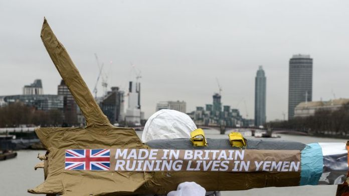 activists march with homemade replica missiles bearing the message 'Made in Britain, destroying lives in Yemen'