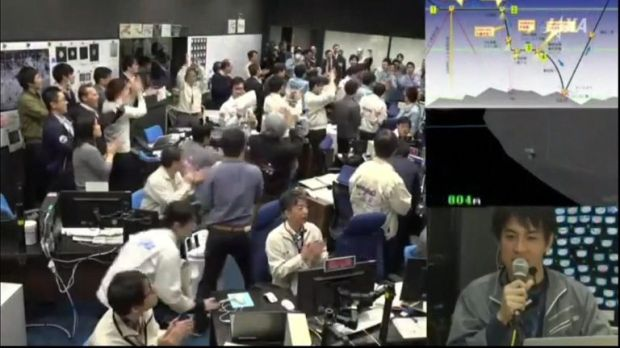 Workers celebrate the spacecraft's landing