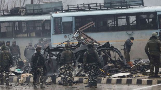 Security forces inspect the remains of a vehicle destroyed in a bomb attack that killed at least 41 soldiers