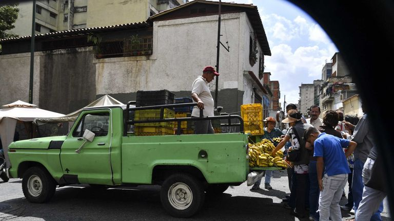 People gather around a man selling bananas in his truck in a street market of Caracas