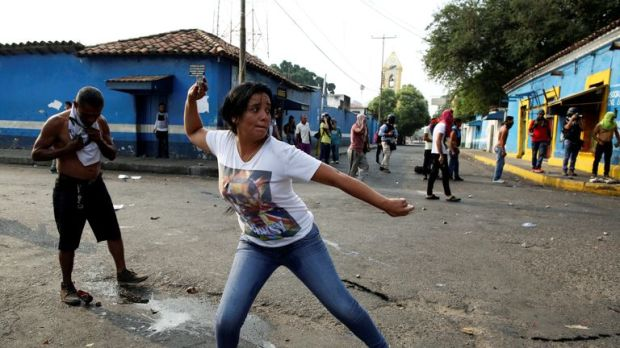 A woman throws an object at police in Urena