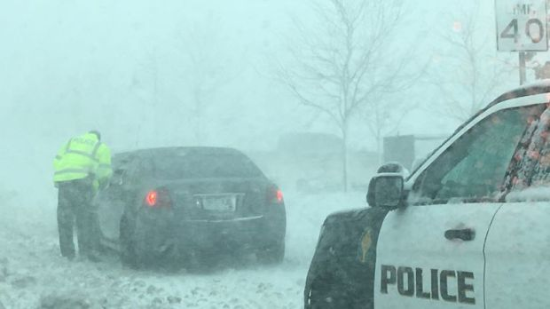 A policeman talks to a driver as snow clogs the roads in Lone Tree, Colorado