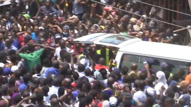 A huge crowd gathers as a child is taken to an ambulance