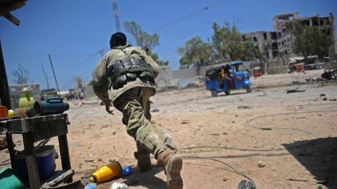 A Somali soldier runs for cover at the scene of two explosions set off near the ministries of public works and labour