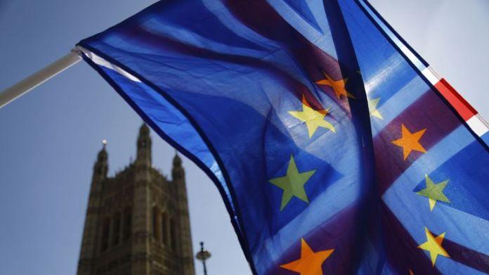 Un activiste agite une combinaison de drapeaux de l'Union et de l'Union européenne près du Parlement, dans le centre de Londres, le 10 avril 2019. - Le principal négociateur de l'UE pour le Brexit a déclaré mardi que la longueur de tout retard dans le divorce du bloc était peut accorder à la Grande-Bretagne dépendra de ce que le Premier ministre Theresa May apporte à un sommet pressant. (Photo de Tolga AKMEN / AFP) (Le crédit photo devrait correspondre à TOLGA AKMEN / AFP / Getty Images)